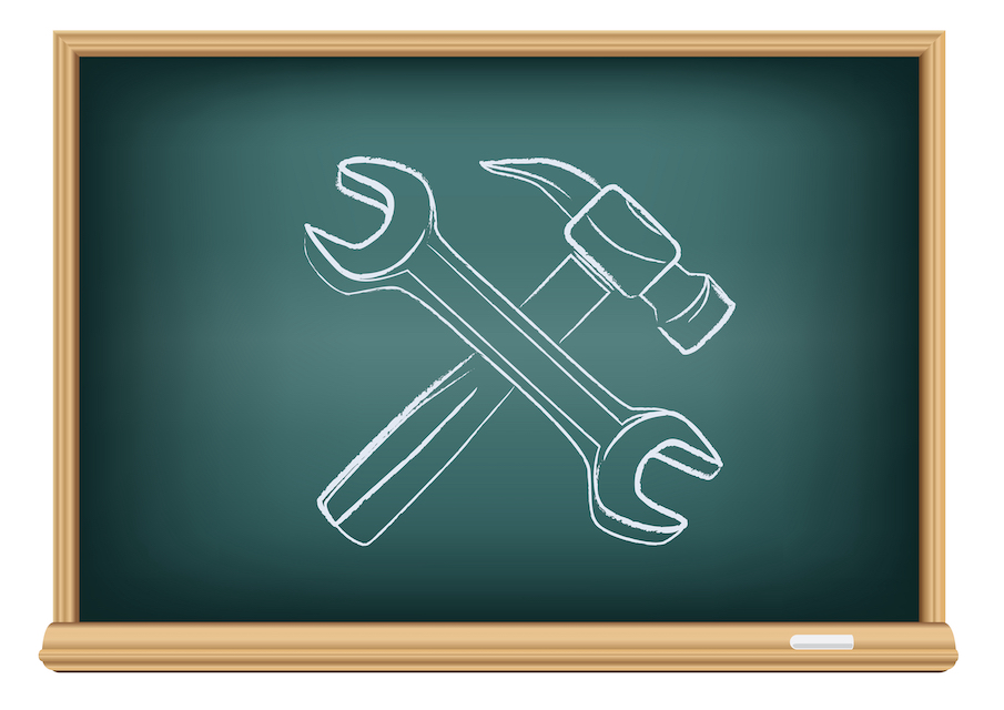 Chalkboard featuring a drawing in chalk of a wrench and hammer, suggesting a metaphor for tools used in school recruitment