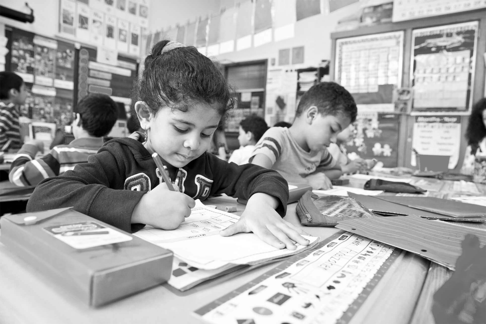 Children writing in workbooks in a classroom.